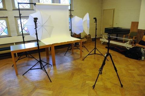 Studioaufbau in der Kirche zur Aufnahme der Krippenfiguren mit Kamerastativ, drei entfesselten Blitzen hinter Durchlichtschirmen und einer Rolle weißer Hintergrundkarton auf einem mobilen Gestell